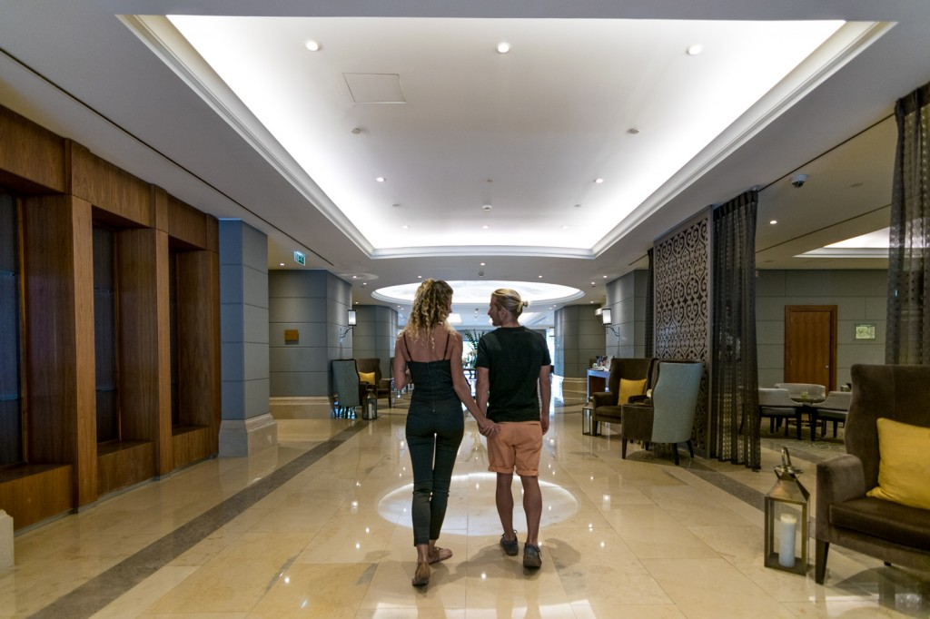 travel couple holding hands walking through lobby at Corinthia Hotel Lisbon